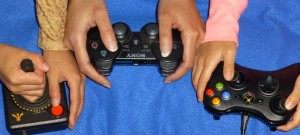 Gamer Mom, Wendy & daughters' hands around various controllers