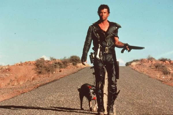 Mel Gibson as Mad Max in Mad Max 2: Road Warrior, stands in the middle of a desert road, gun in hand, a brace on his leg, and a dog by his side.