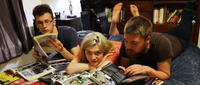 The three members of Sister Wolf lay on a bed reading a pile of comics