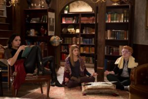 Carmilla, Laura, and LaF sit around the library