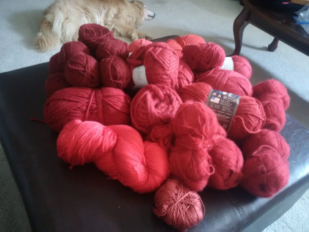 My red yarn stash that nearly overflows my ottoman, with Ollie laying in the background.