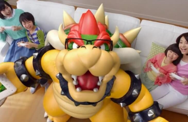 Bowser in glasses on a couch with a Japanese family.
