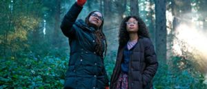 A Wrinkle in Time director Ava Duvernay and lead Storm Reid standing together in a forest.