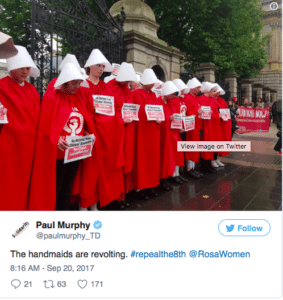 Tweet of Pro-Choice Protestors in Ireland dressed like Handmaids in the white bonnets and red cloaks standing in protest with heads bowed
