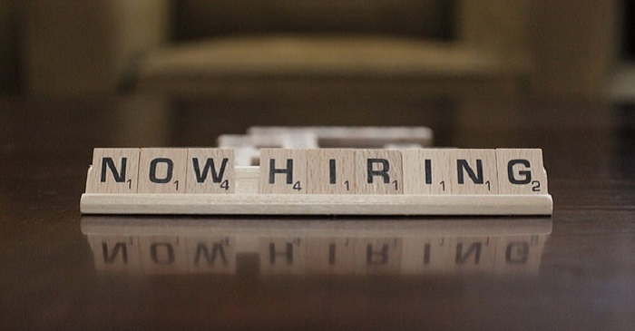 "Scrabble letters spell out ""NOW HIRING"""