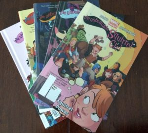 Five comic books laid out on a wooden table (Unbeatable Squirrel Girl, topped by Volume 1, Squirrel Power)
