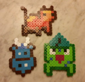 Photograph of perler bead art: a shield logo, a happy bulbasaur, and an orange cat.