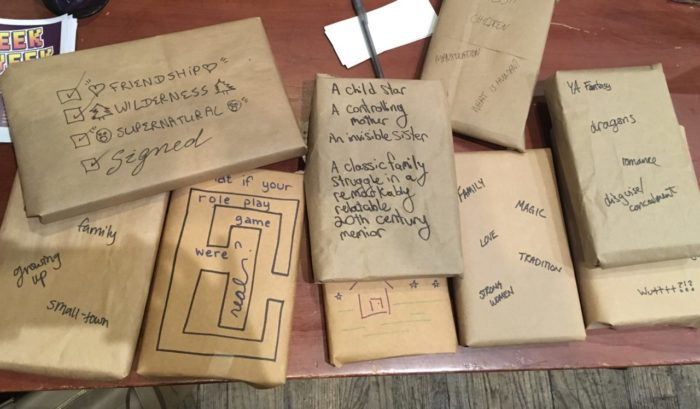wrapped books on a table, each of which has descriptors written on it