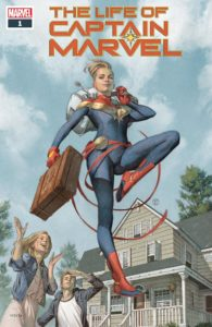 Captain Marvel, carrying a suitcase, lands in front of a rural house