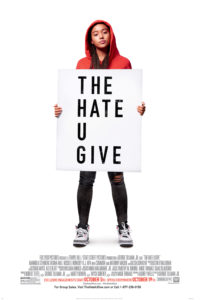 Amandla as Starr Carter holding a sign reading The Hate U Give