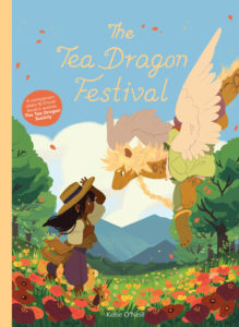 Cover of The Tea Dragon Festival - A dark skinned younth with long dark hair approaches a winged dragon from across a field of red flowers