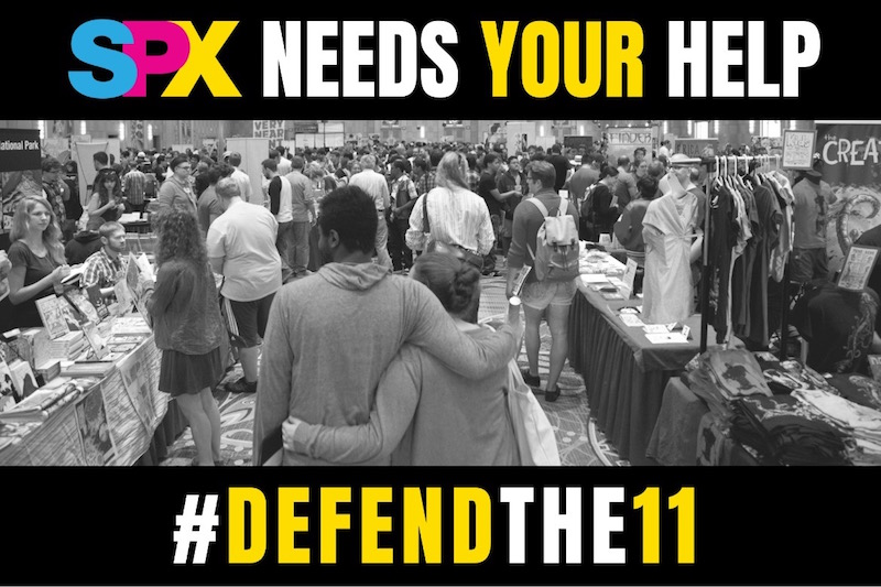 "A black and white photo of a convention hall between two horizontal black bars. On the top bar, the text reads ""SPX NEEDS YOUR HELP;"" on the bottom bar, the text reads ""#DEFENDTHE11."" DefendThe11, SPX. Image created by SPX staff."