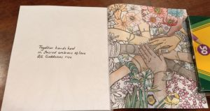 Left page text: Together hands heal in sacred embrace of love All goddesses rise. Right coloring page: Incomplete coloring of nine women's hands overlapping at the center and framed with riotous flowers.
