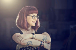 A photograph of V.E. Schwab, a redhaired woman with bird tattoos on her arms, smiling at something to her left.
