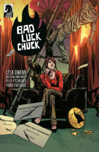 A young girl with short red hair sits casually on a chair as disaster strikes all around her in the form of falling ladders, curtains catching fire, broken lights in Bad Luck Chuck (Dark Horse Comics, March 2019)