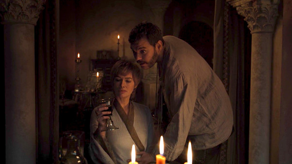 Cersei sits with a glass of wine; Euron leans over her with his hand on her belly.