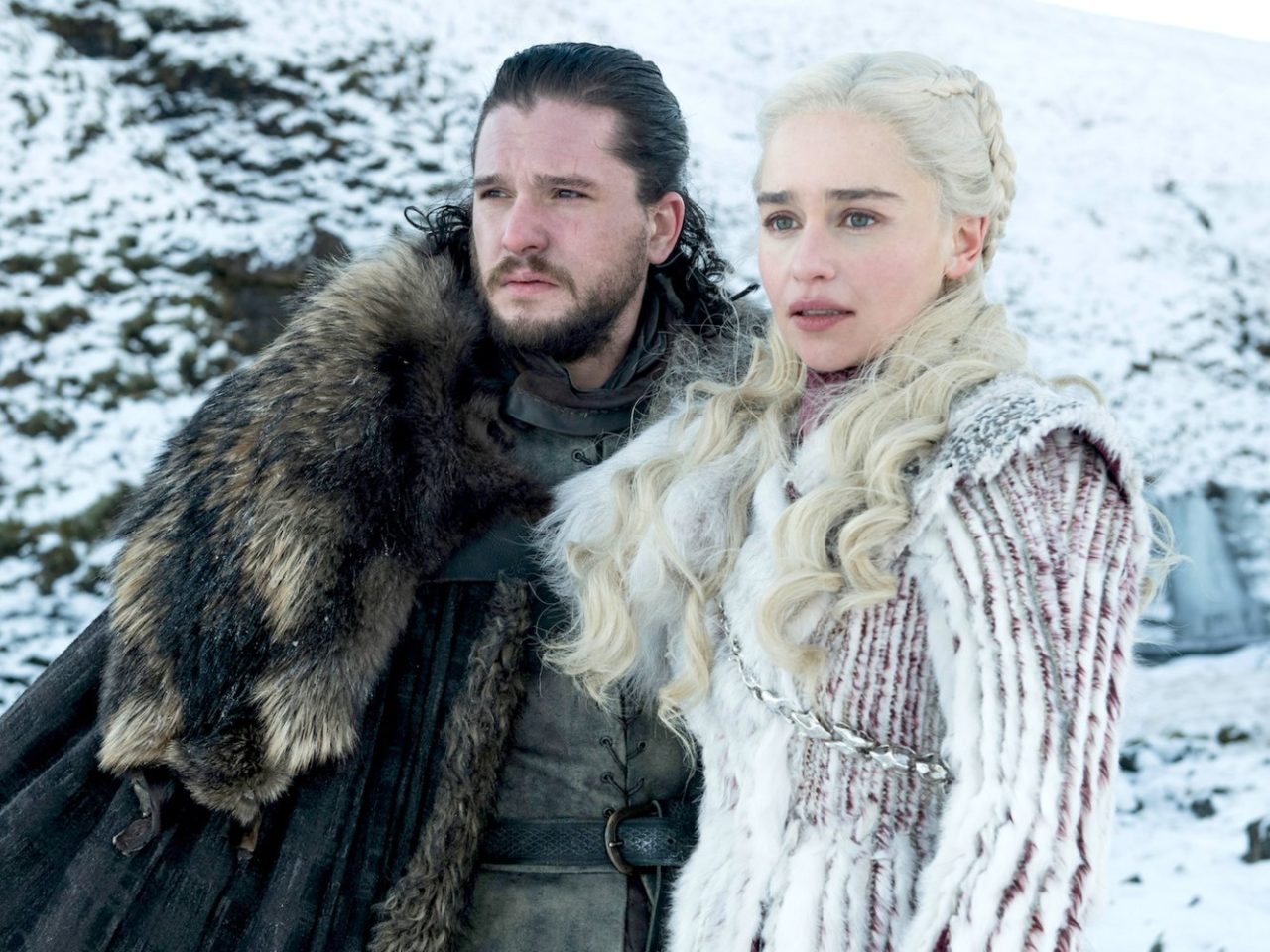 Dany (Emilia Clarke) and Jon (Kit Harrington) stand together with snow covered mountains in the background