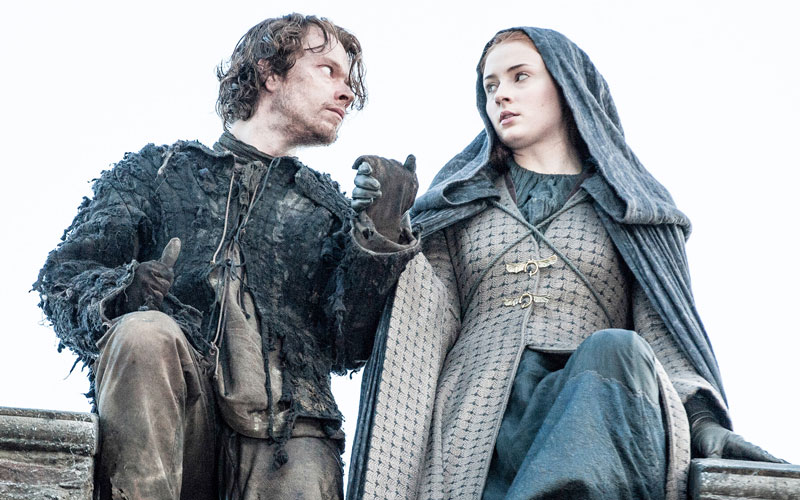 Theon and Sansa stand atop a wall, prepared to risk their lives to leap to safety