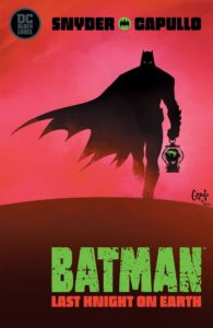 Batman silhouetted holding the severed head of the Joker