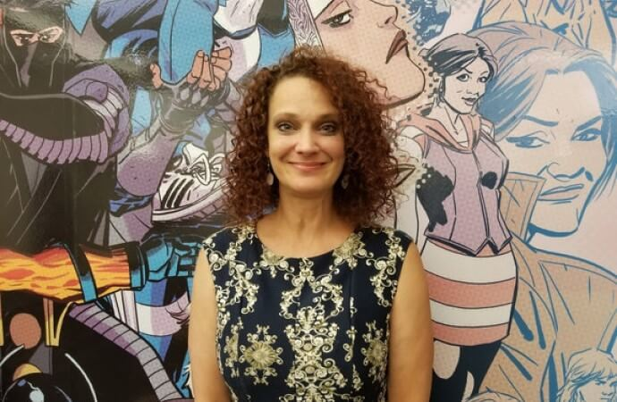 Editor Lysa Hawkins stands smiling in front of a mural of Valiant characters