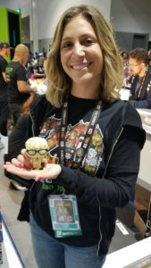 Megan Harris at the ThinkGeek booth at SDCC 2019 holding a Funko of Post-it Note Man from the movie Office Space
