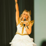 Ashley Eckstein raises her fist in a power pose