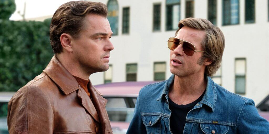 Leonardo DiCaprio and Brad Pitt stand next to each other as their characters Rick Dalton and Cliff Booth
