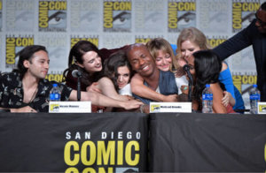 The cast of Supergirl (Jesse Rath, Katie McGrath, Nicole Maines, Melissa Benoist, Andrea Brooks, Azie Tesfai and David Harewood) hugging an emotional Mehcad Brooks