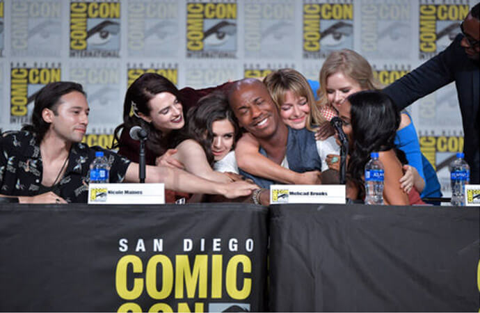 The cast of Supergirl (Jesse Rath, Katie McGrath, Nicole Maines, Melissa Benoist, Andrea Brooks, Azie Tesfai and David Harewood) hugging an emotional Mehcad Brooks