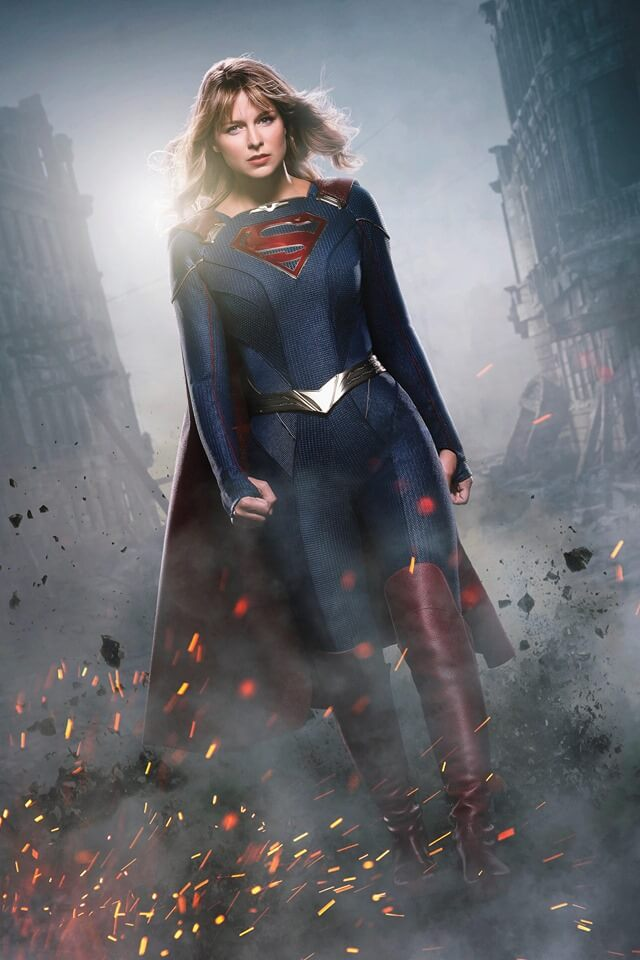 Supergirl in a pantsed costume walking through destruction