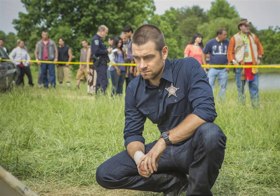 Antony Starr as Sheriff Lucas Hood crouches to inspect a crime scene