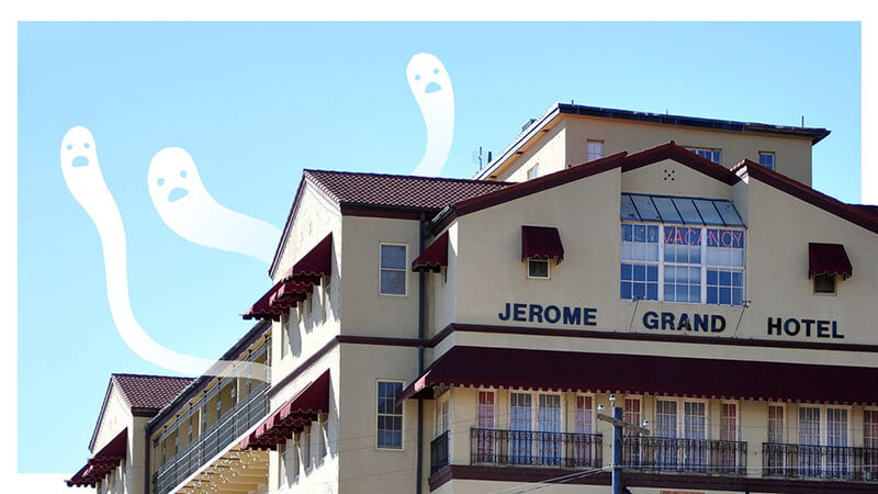 The main Kickstarter image for The Book of Ghosts. Drawn on cartoon ghosts slither out of a the roof of a photo of the hotel. The Book of Ghosts: Jerome Grand Hotel, Meredith McClaren, 2019