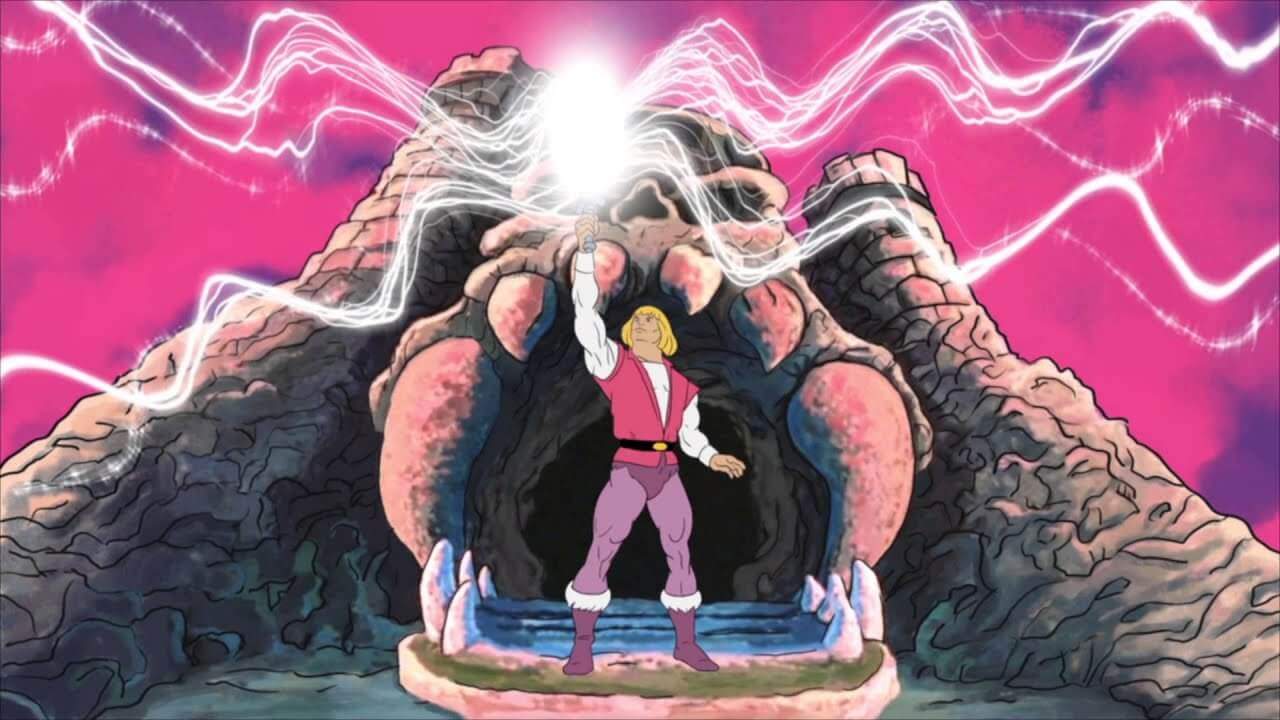 Prince Adam stands in front of Castle Grayskull, holding aloft his sword as magical light emits from the blade