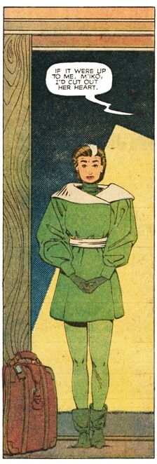 Rogue wearing a large green tunic stands in a doorway
