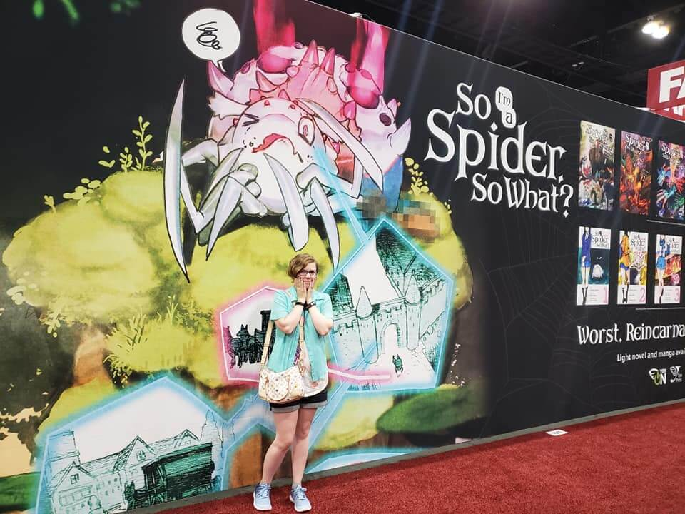"Jennifer McKeon standing in front of a banner that reads ""So I'm a spider so what?"""