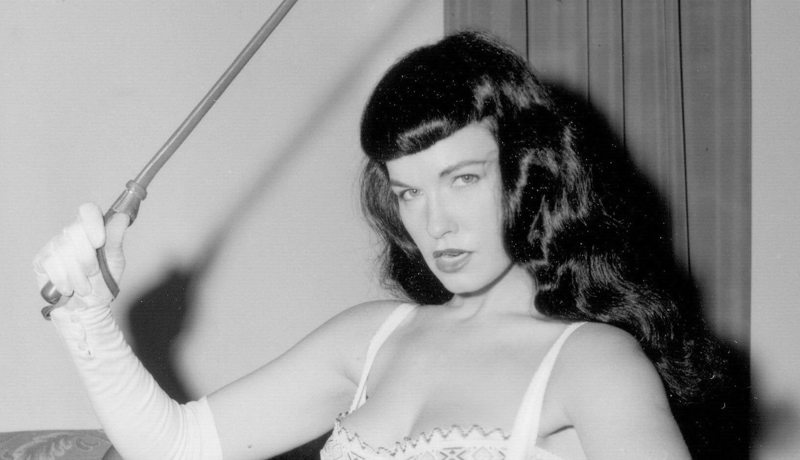 A black and white photo of Bettie Page with a riding crop