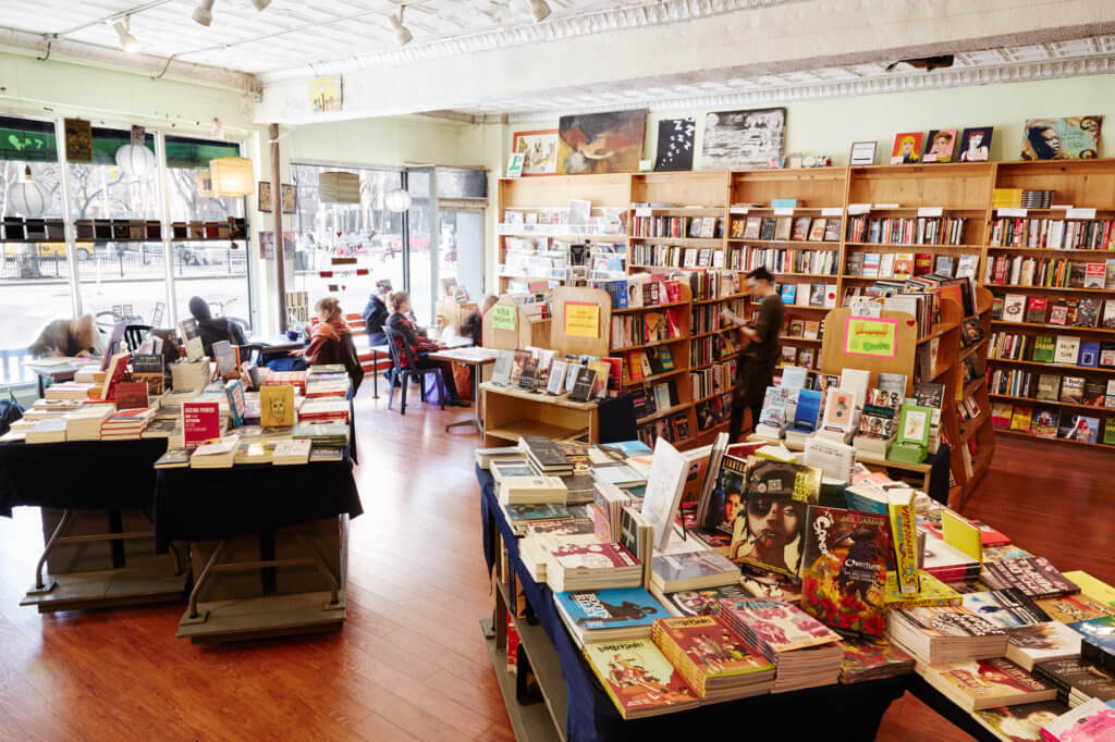 A bookstore features a vast inventory of books and print material. Tables and shelves are completely adorned. A stream of light bleeds through big windows at the store's front, which are on the left side of the image. Small tables with several people sitting in them.