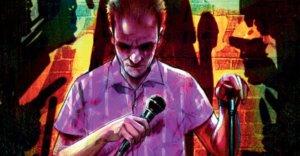 Cover for Dying is Easy, IDW - A man looks down with a grim expression, holding a mic