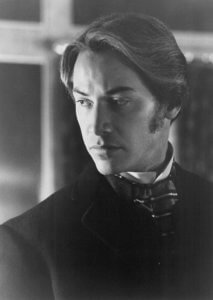A black-and-white still of Keanu Reeves as Jonathan Harker, looking pensive