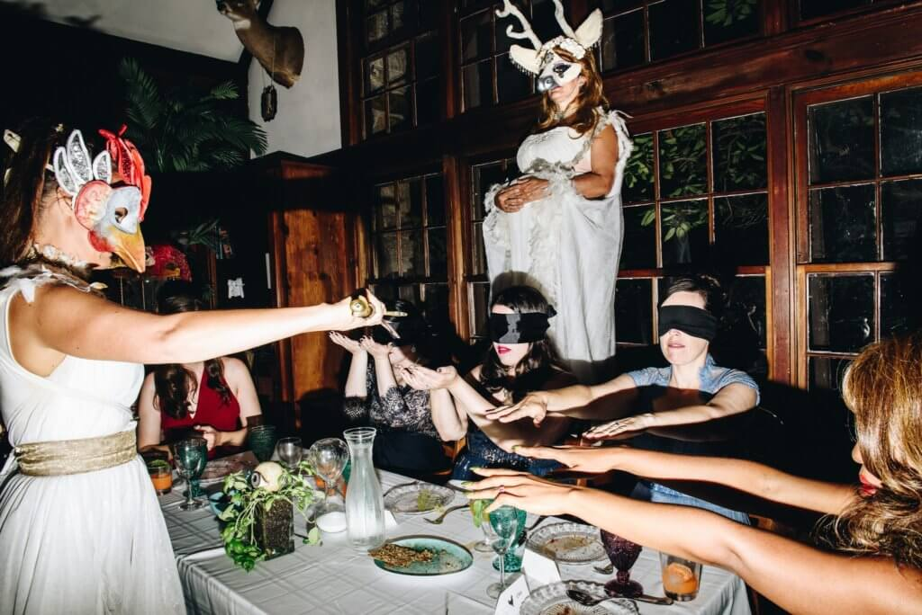 Blindfolded guests at a dinner table reach their hands out to one another. A woman dressed in white wearing a horned mask stands above them