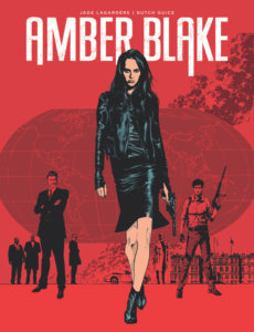 Cover for Amber Blake. IDW Publishing October 2019 - A woman in a black jacket and skirt walks towards the viewer holding a gun at her side, against a red background