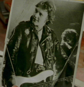 A photo of young Giles wearing a leather jacket and playing the guitar.
