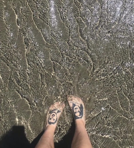 Rosie's feet with heads of the two characters are in water at a beach