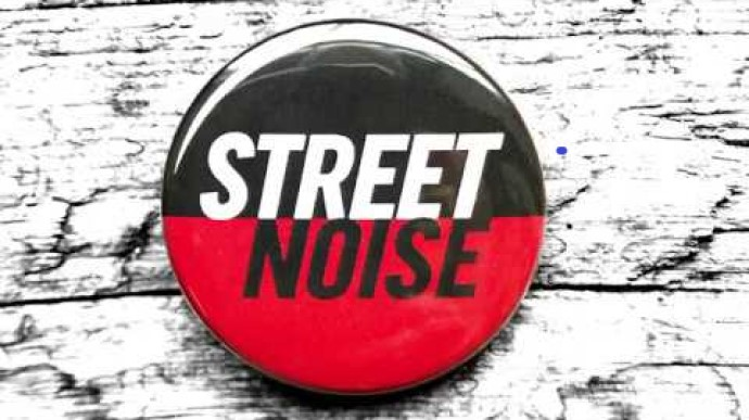 "red and black button with the words ""street noise"" in white and black"