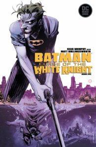 Joker wearing a Batman shirt and holding a long pistol