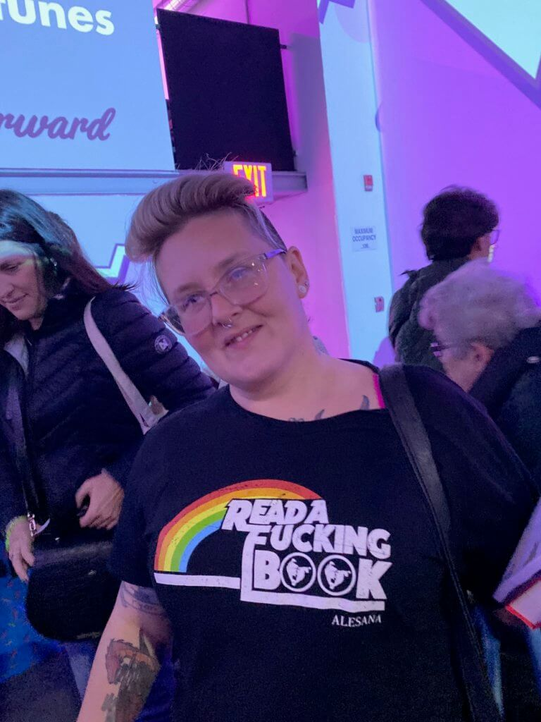 """a person displaying a shirt that reads """"read a fucking book"""" with the Reading Rainbow rainbow"""