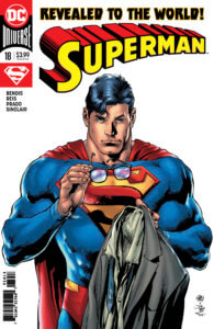 Superman holding his glasses and jacket