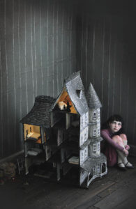 Creepy little girl behind dollhouse