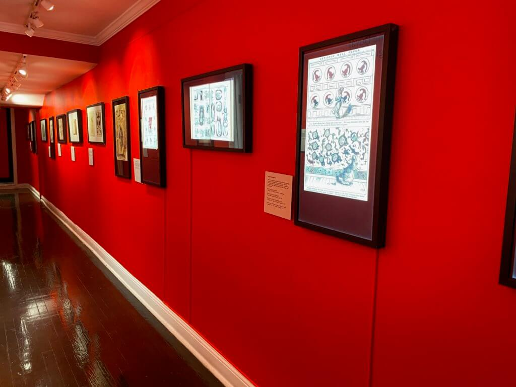 a long hall is painted red and has framed black and white work on the wall.