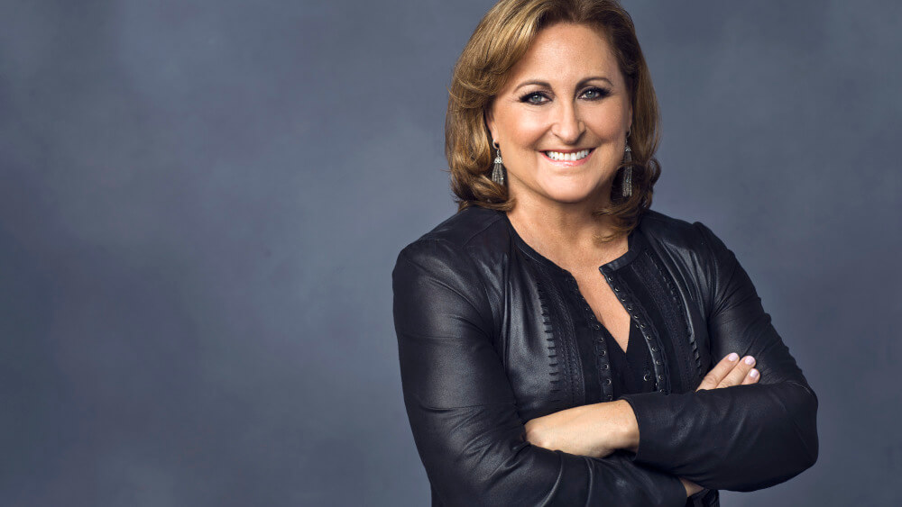 Portrait of Cyma Zarghami. She has shoulder length brown hair, is smiling and wearing a black leather jacket.